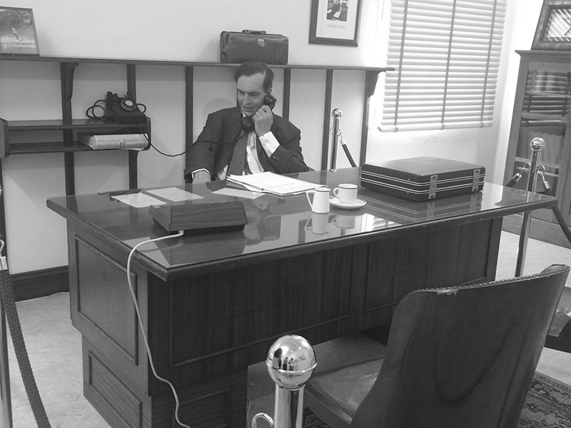 wax figure sitting at desk and talking on his phone